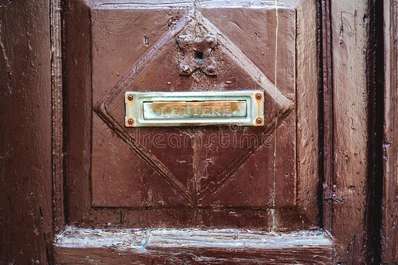 The letter sign is a symbol of the mailbox attached to the brown wooden door of the house. Outdated methods of correspondence royalty free stock image