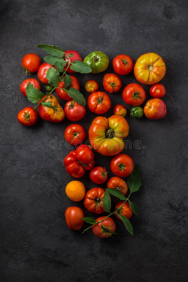 Letter T made with ripe tomatoes on a black background, creative flat lay healthy food concept royalty free stock images