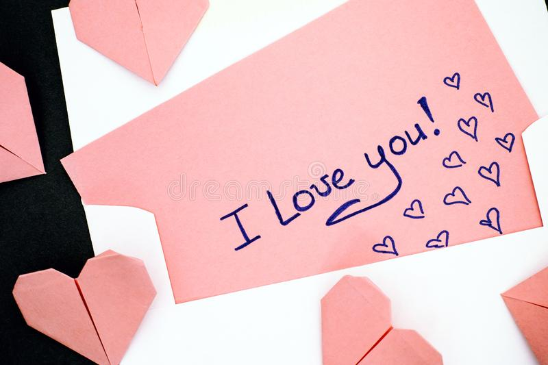 Letter with text I Love You! with envelope and pink origami hear. Ts. Black background. Close-up stock images