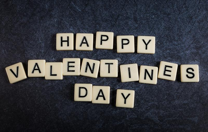 Letter tiles on black slate background spelling happy valentines day royalty free stock photo