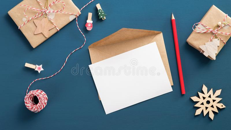 Letter to Santa Claus mockup. Flat lay blank paper card, craft envelope, gift box, wooden decorations on blue background. Top view stock photography