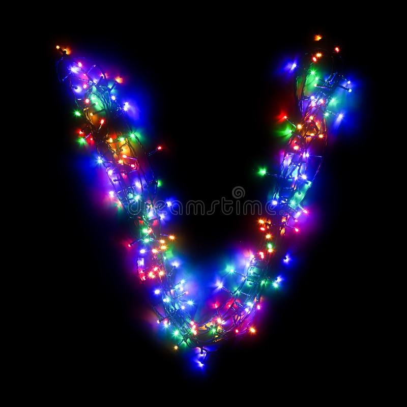 New Year`s alphabet. The letter `V` of the English alphabet from a multi-colored electric garland on a black isolated background. New Year`s alphabet.Wreath of royalty free stock photography