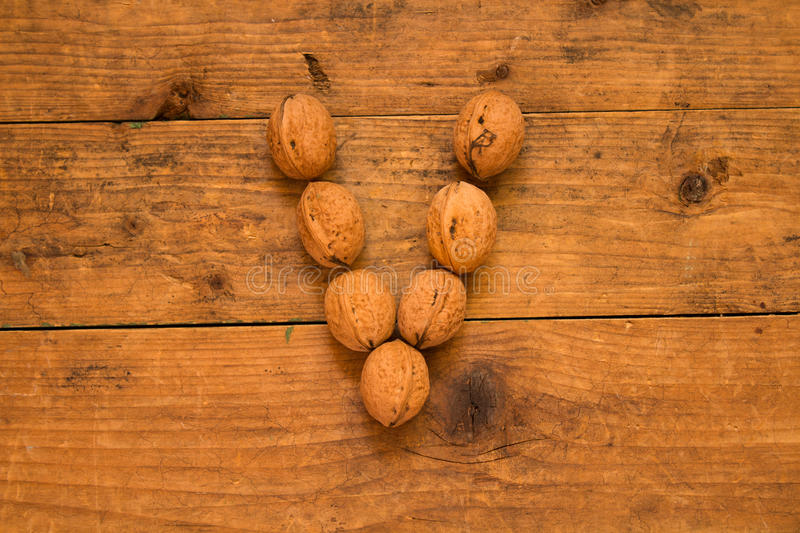 Letter V made from walnuts. Color top view of english alphabet made from walnuts on a wooden table. Letter V stock image