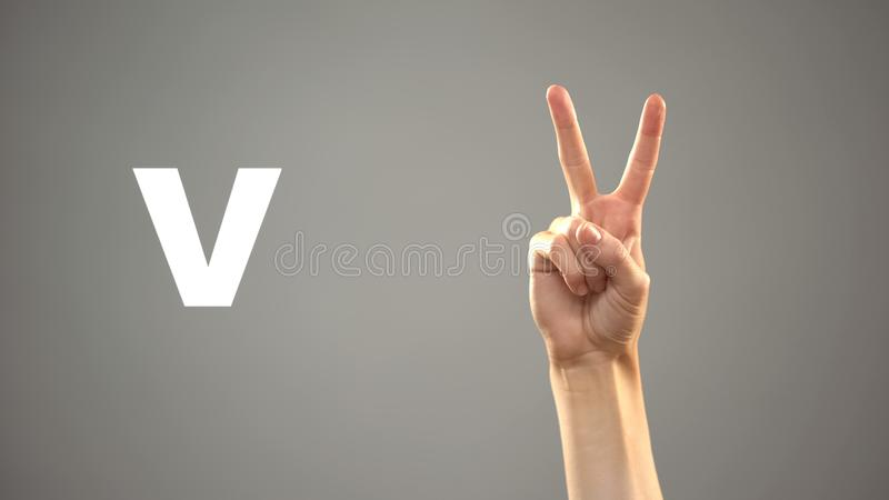 Letter V in sign language, hand on background, communication for deaf, lesson stock photos