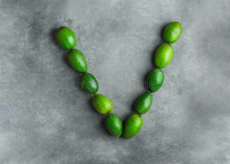Letter V for vegan vegetables vitamins vitality made from ripe raw avocados on dark gray stone background. Food typography royalty free stock images