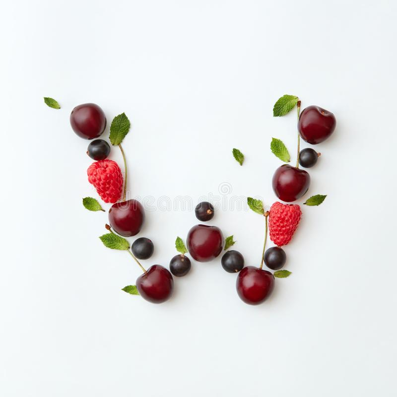 Summer berries pattern of letter W english alphabet from natural ripe berries - black currant, cherries, raspberry, mint royalty free stock image