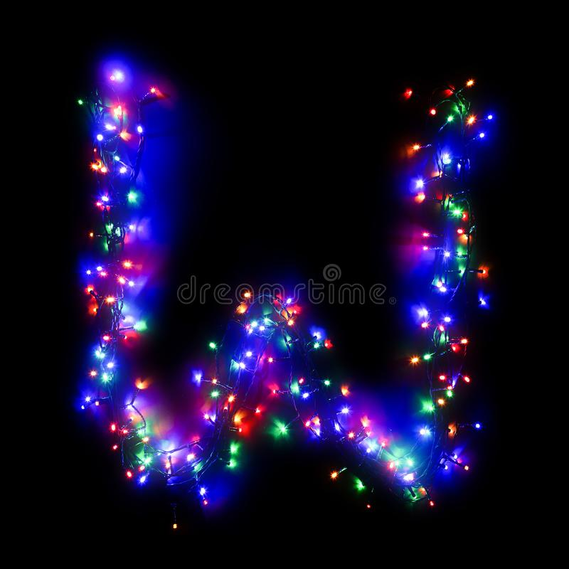 New Year`s alphabet. The letter `W` of the English alphabet from a multi-colored electric garland on a black isolated background. New Year`s alphabet.Wreath of royalty free stock photos