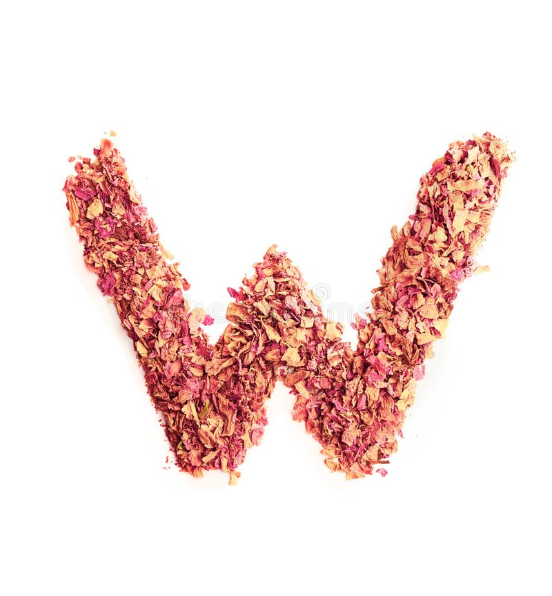 Letter W made of dried rose petals, isolated on white background. Food typography, english alphabet. Design element. Letter W made of rose petals, isolated on royalty free stock photography