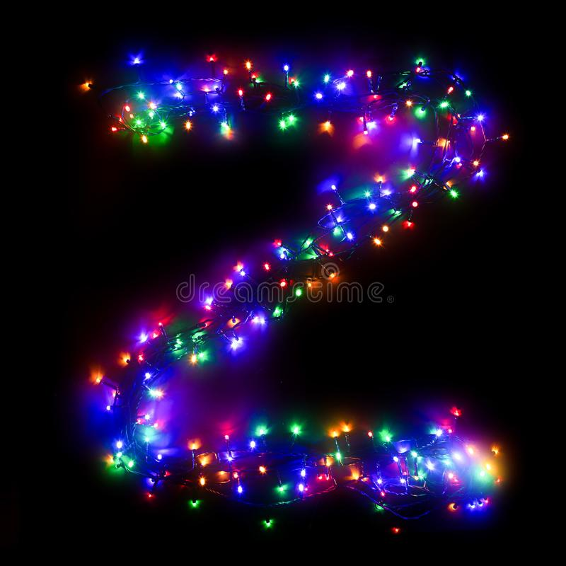 New Year`s alphabet. The letter `Z` of the English alphabet from a multi-colored electric garland on a black isolated background. New Year`s alphabet.Wreath of royalty free stock images