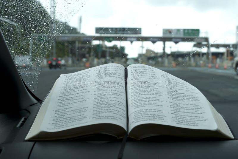 Lettera aperta la Sacra Bibbia nel salmo 91 Sfondo sfocato con casello sulla superstrada fotografie stock