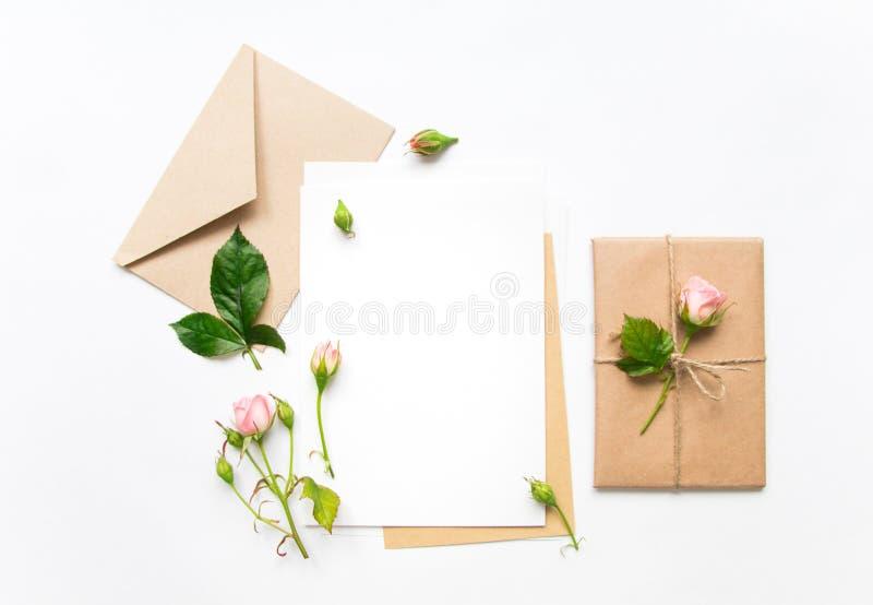 Lettera, busta e regalo su fondo bianco Carte dell'invito, o lettera di amore con le rose rosa Concetto di festa, vista superiore fotografia stock libera da diritti