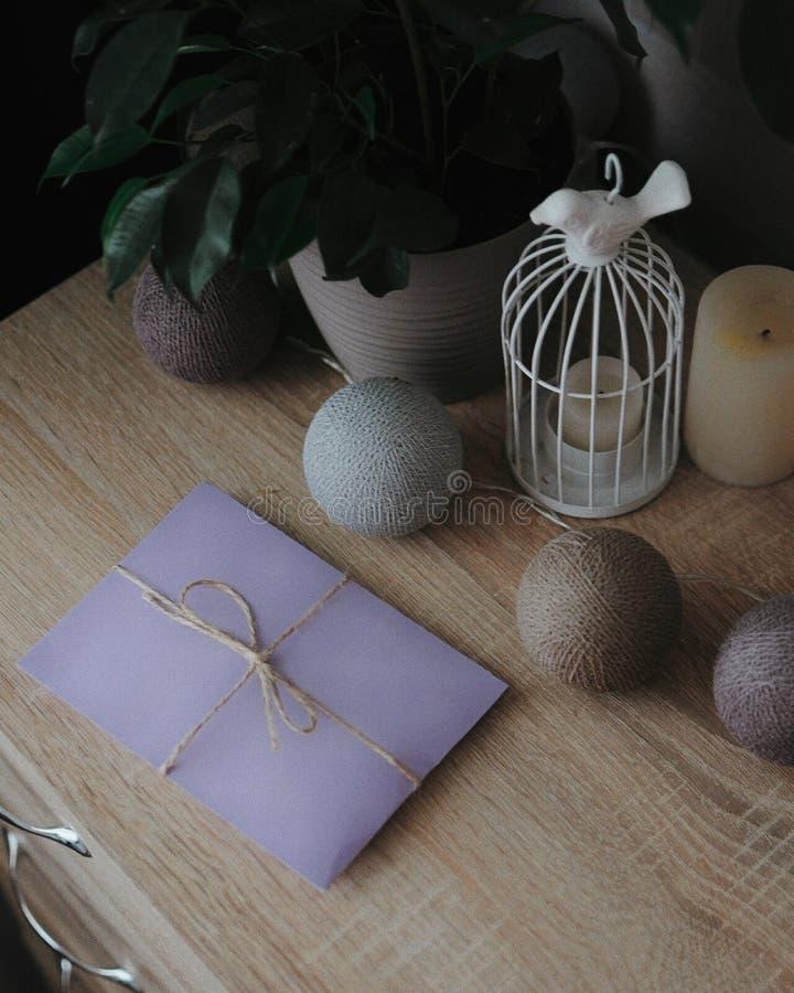 Lettera in busta porpora sulla tavola con le lampadine, la candela e l'albero decorativi Invito del regalo fotografia stock