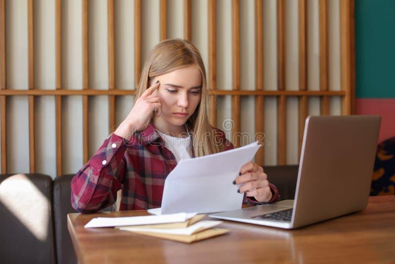 Lettera della lettura della giovane donna alla tavola in caffè consegna di posta fotografie stock