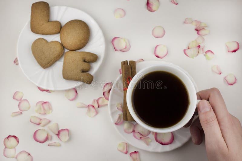 Lettera di amore da un biscotto, mano che tiene una tazza di caffè su uno spuntino bianco del fondo fotografia stock