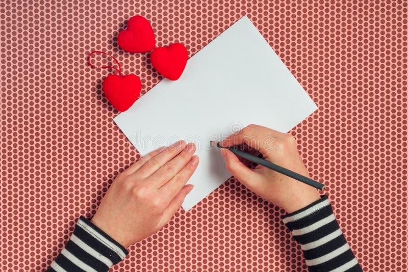Lettera di amore di scrittura della donna per il giorno di biglietti di S. Valentino immagini stock