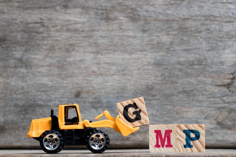 Lettera di plastica gialla G della tenuta del bulldozer per completare parola GMP su fondo di legno fotografia stock libera da diritti