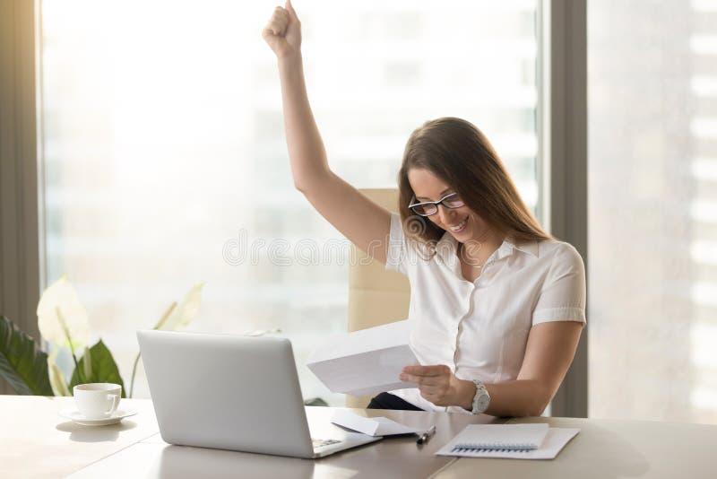 Lettera felice della lettura della donna di affari in ufficio fotografie stock
