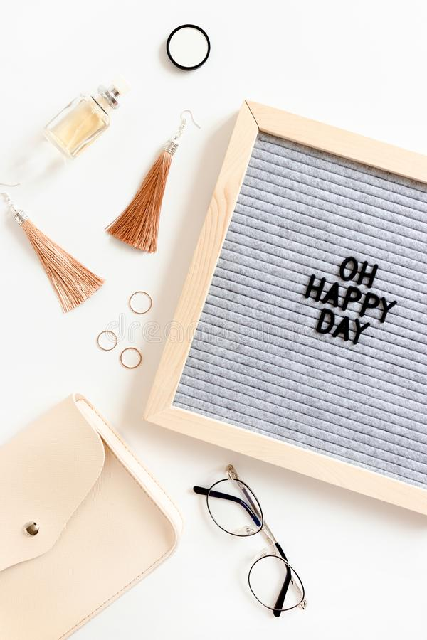 Letterboard with quote Oh happy day. Fashion flat lay of handbag, earrings, bottle of perfume and glasses. On white desk stock photography