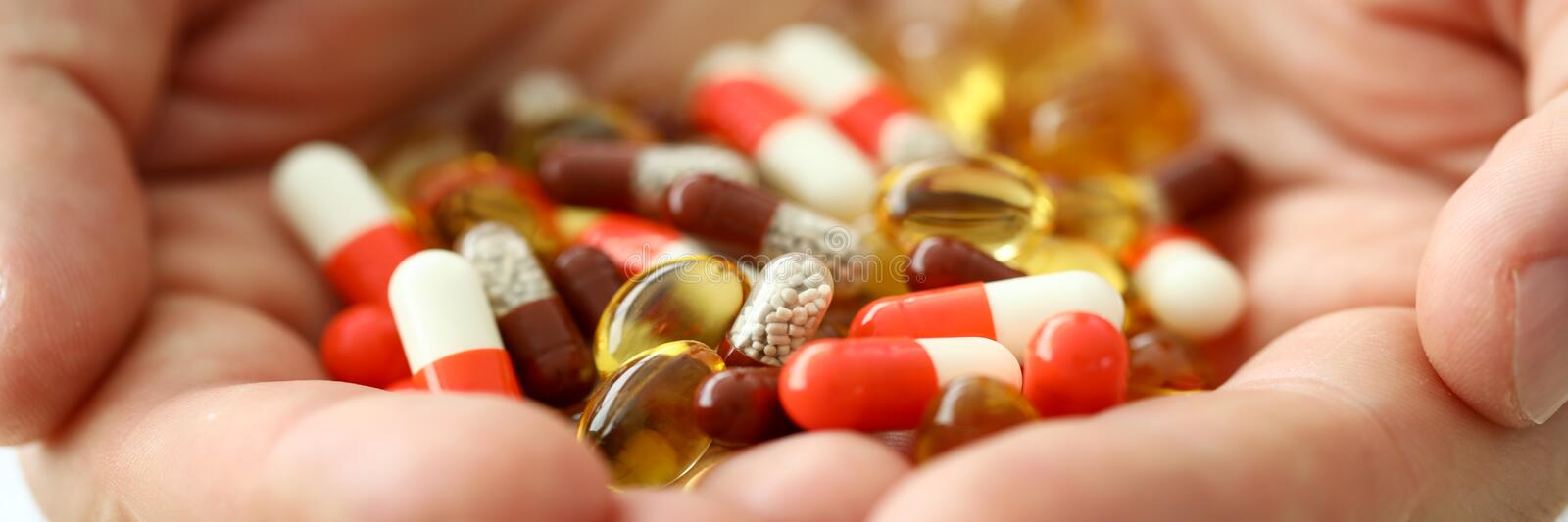 Man hold in arms set of different pills close-up stock images