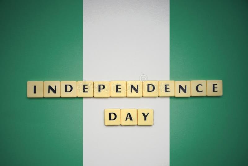 Lettere con la festa dell'indipendenza del testo sulla bandiera nazionale della Nigeria fotografia stock libera da diritti