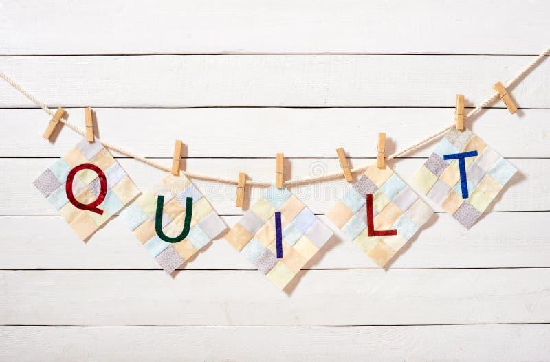 Lettere cucite, combinate come la trapunta di parola, allegata con le mollette da bucato su una corda immagini stock