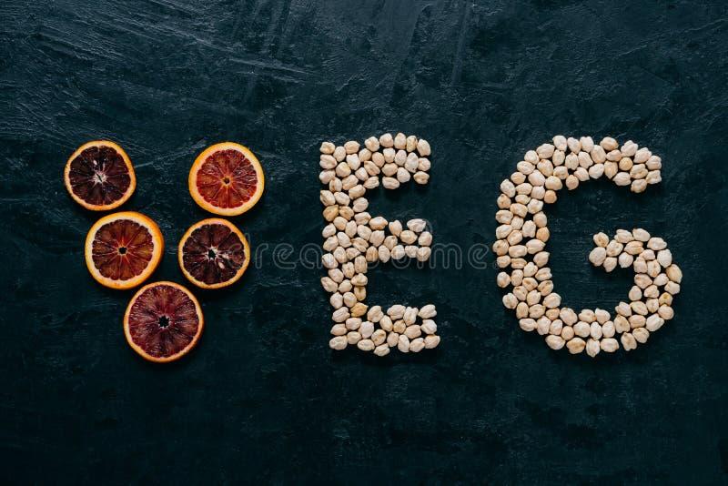 Lettere dell'alimento Cece e fetta di agrumi nella forma di lettere del veg su fondo scuro Ingredienti organici per i vegetariani fotografia stock libera da diritti
