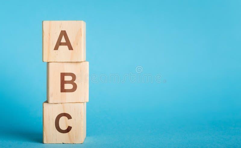 Lettere di ABC dei blocchi di legno nella forma della colonna su fondo blu fotografia stock