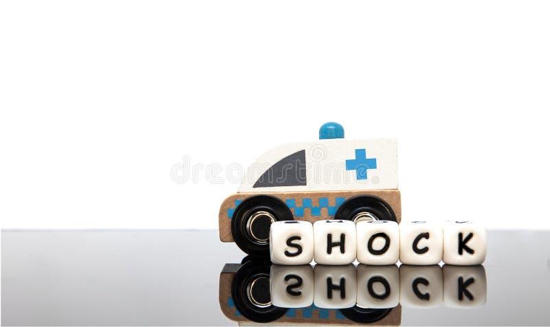 lettere di alfabeto che compitano la scossa di parola e un'ambulanza del giocattolo fotografia stock libera da diritti