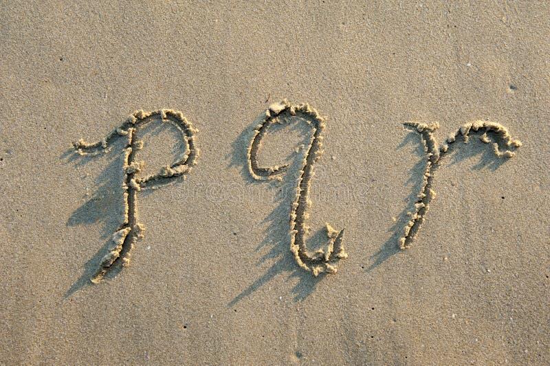 Lettere di alfabeto in sabbia sulla spiaggia fotografie stock libere da diritti