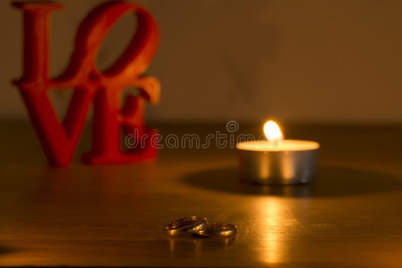 Lettere di amore rosse su fondo bianco a sinistra con due anelli e candele fotografia stock libera da diritti