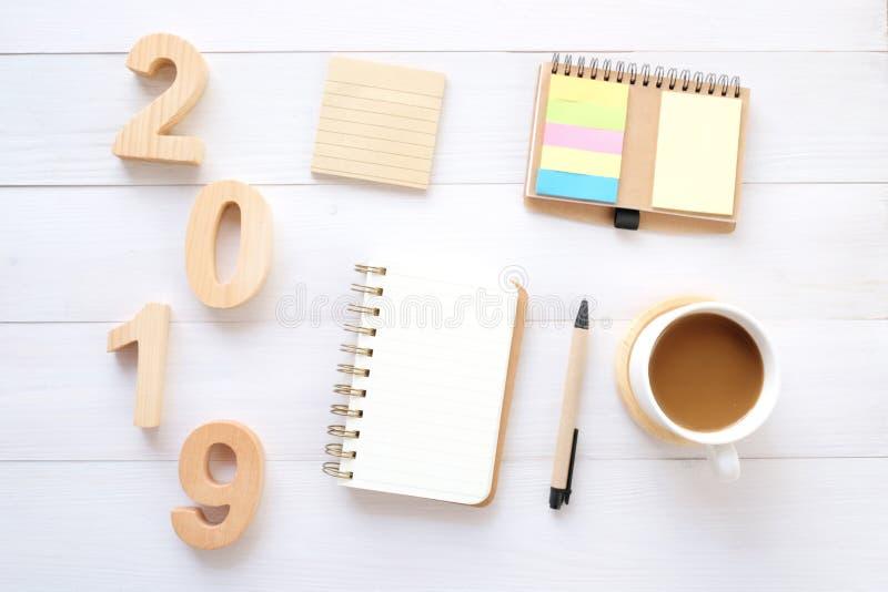 2019 lettere di legno, carta in bianco del taccuino e caffè sul fondo bianco della tavola, una derisione di 2019 nuovi anni su, m fotografie stock