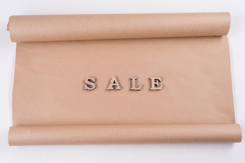 Lettere di legno di parola di un estratto di VENDITA, carta kraft d'annata del fondo fotografia stock libera da diritti