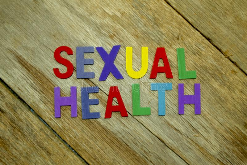 Lettere di legno variopinte di alfabeto di SALUTE SESSUALE di parola messe su fondo di legno Sanità e concetto medico immagine stock libera da diritti