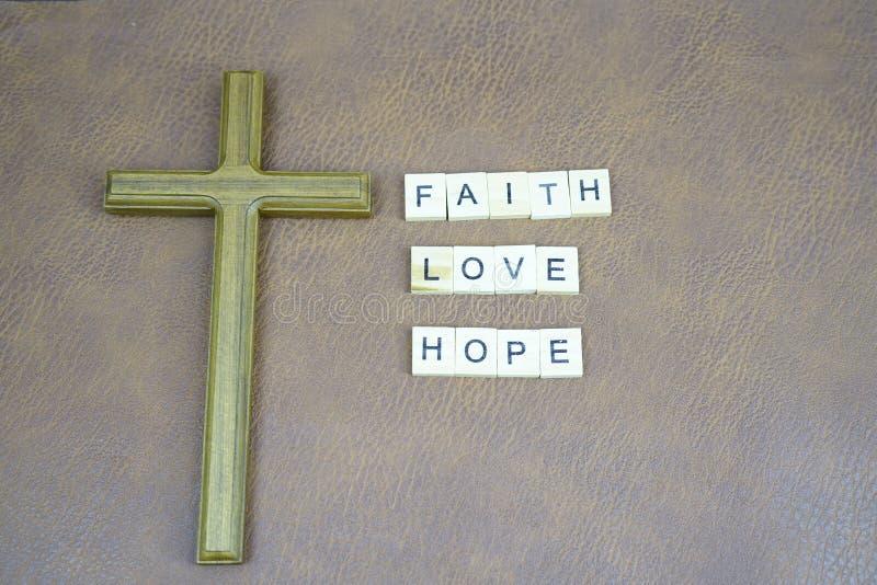 Lettere di speranza di amore di fede ed incrocio santo sulla tavola di cuoio fotografie stock