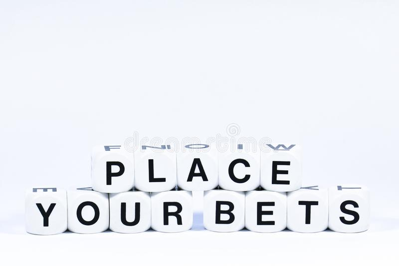 Lettered dice spelling out the phrase place your bets stock photo
