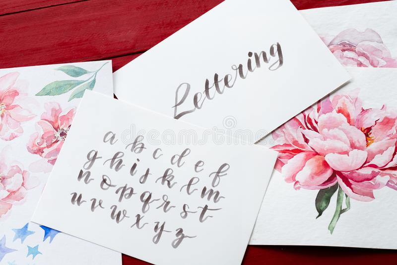 Lettering art calligraphy handwritten cursive. Lettering art and calligraphy craft. handwritten italic cursive. drawn alphabet and watercolor floral paintings stock image