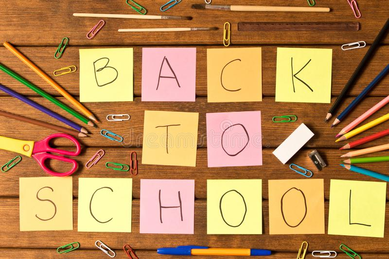 Lettering back to school and various school supplies on wooden b stock photography