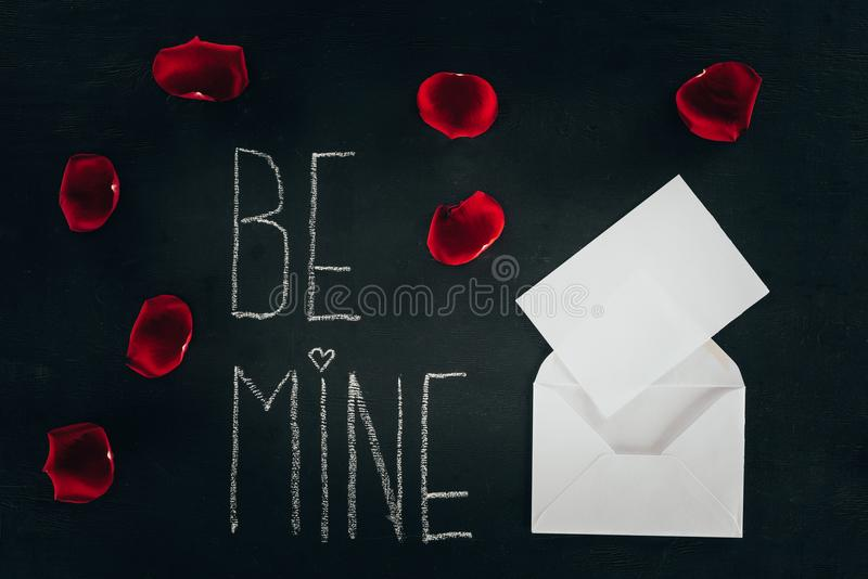Lettering BE MINE surrounded with rose petals and envelope on black surface stock photography