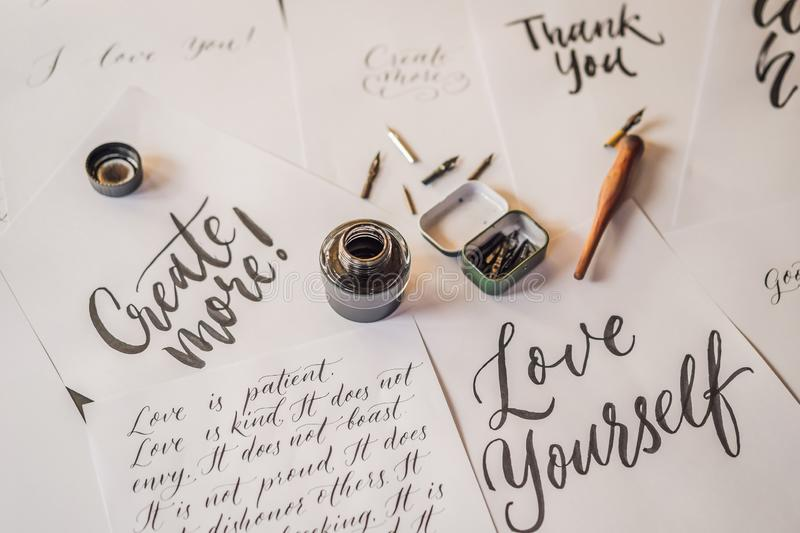 Lettering, calligraphy, writes phrase on white paper. Inscribing ornamental decorated letters. Calligraphy, graphic royalty free stock photos