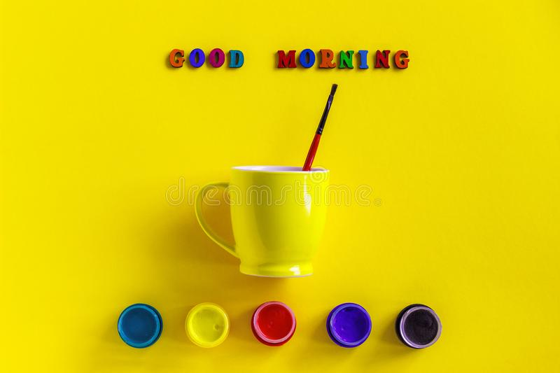 Lettering Good morning, jars gouache and yellow cup with paintbrush. Concept. Lettering Good morning from colorful letters, jars gouache and yellow coffee cup stock photos