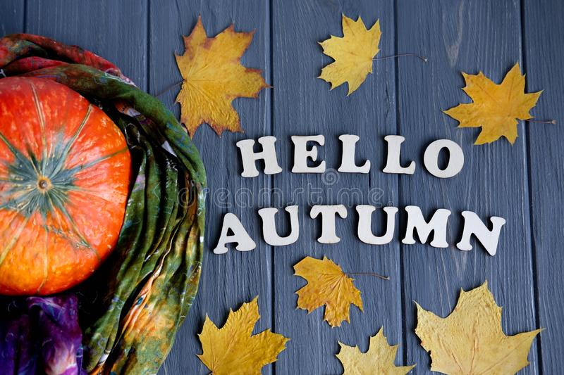 Lettering Hello Autumn from wooden letters. Autumn banner with pumpkin and autumn yellow leaves on a gray wooden background royalty free stock photos