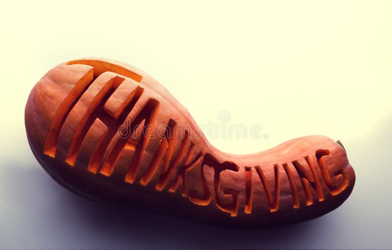 Lettering word `Thanksgiving` on a pumpkin stock image