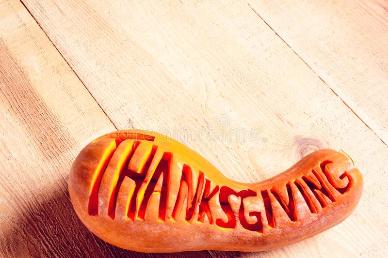 Lettering word `Thanksgiving` on a pumpkin stock photography