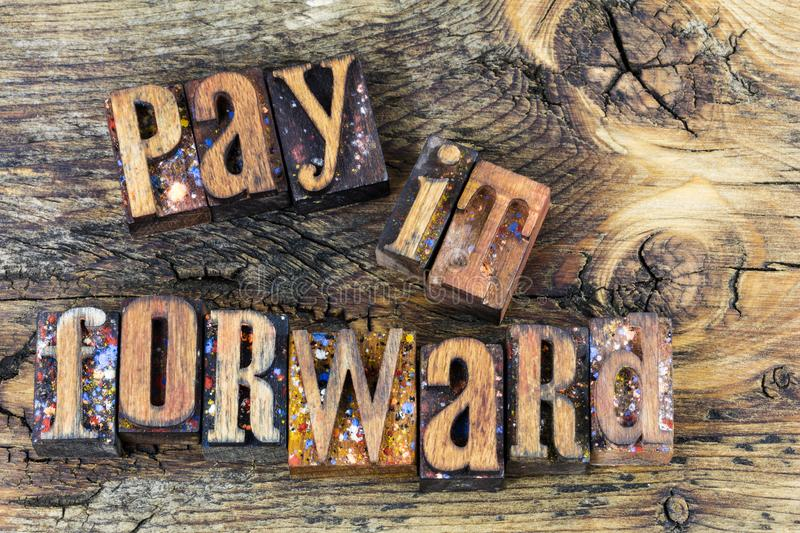 Pay it forward message letterpress. Letterpress type text message wood block letters words pay it forward volunteer volunteering help helping charitable giving stock images