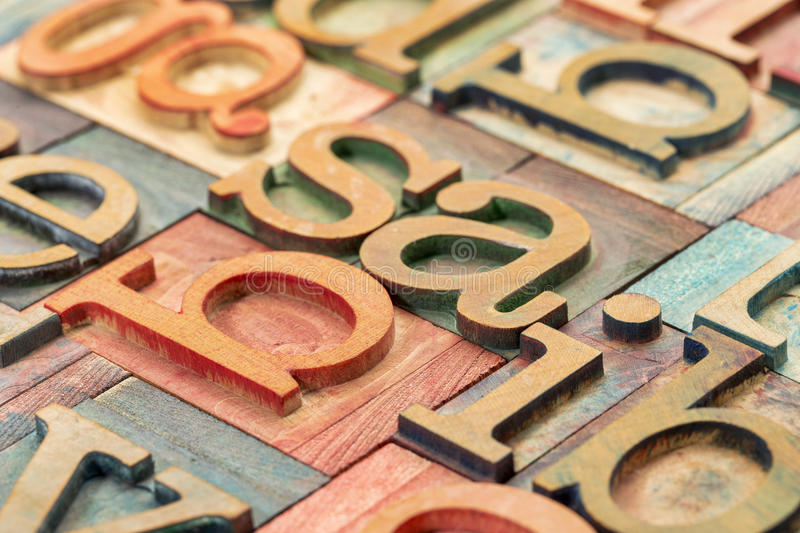 Letterpress wood type abstract. Alphabet abstract in letterpress wood type printing blocks stained by color inks royalty free stock images
