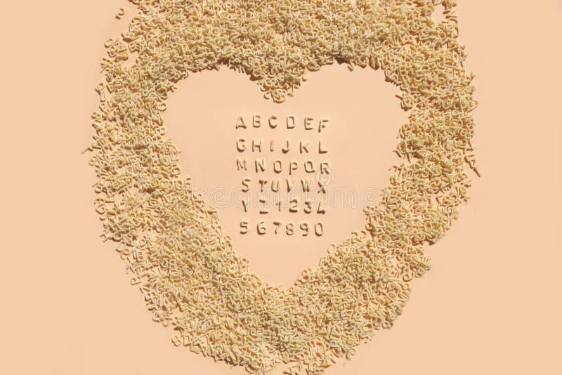 Letters of alphabet of pasta for kids food on light pink background. Pastel color for children`s meals.  stock images
