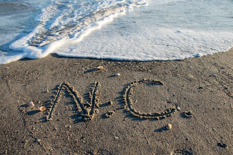 North Carolina sand, beach and water. The letters N and C written in the sand on a North Carolina Beach as waves and water roll in royalty free stock photo