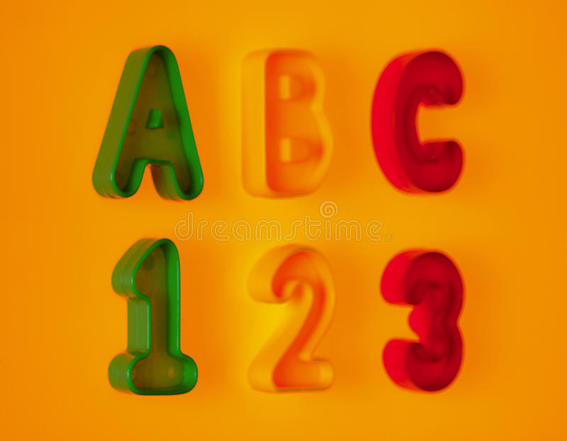 Letters and numbers on yellow background. ABC letters and 123 numbers on yellow background stock photography