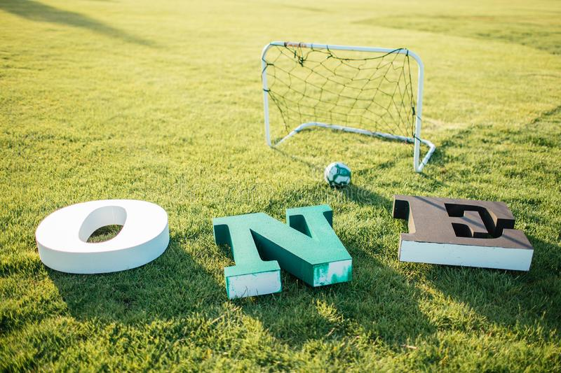 Letters O N E of white, green and black colors lying on a green grass near football goal. Decorations for photos 1 year babies. stock photo