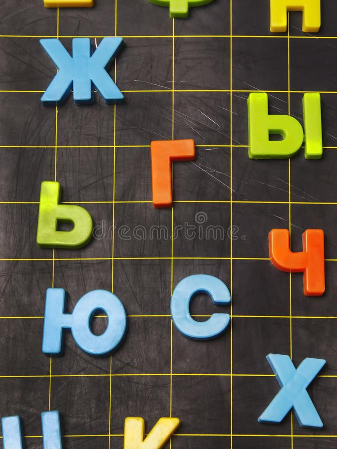 Russian alphabet letters scattered on the board. The letters of the Russian alphabet are scattered on a black board to study at school stock images